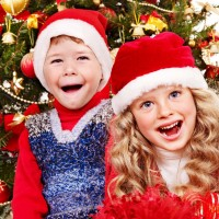 Children in Santa hat with gift box .