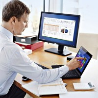 Man at Desk with Latitude 12 Touch 7000 Series and U2412M Monito
